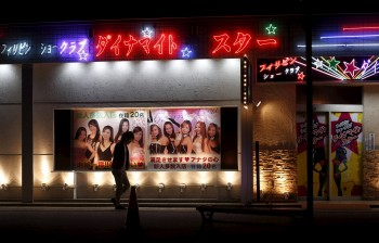 A man walks outside a club with an advertisement depicting women from the Philippines in the red light district in Ota, Gunma prefecture, north of Tokyo, Japan, April 24, 2015. Picture taken April 24, 2015. To match Special Report JAPAN-SUBARU/ REUTERS/Yuya Shino