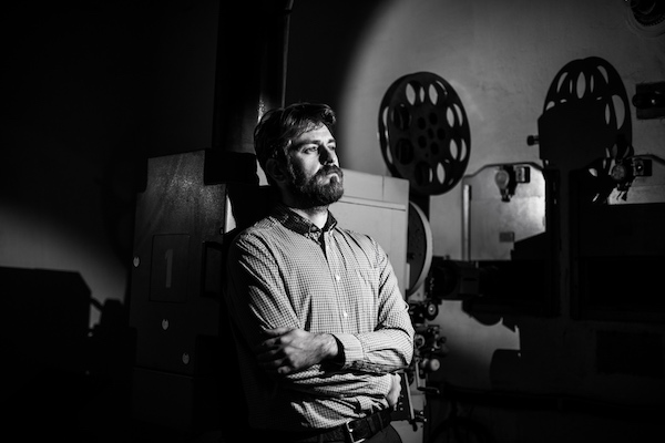 beautiful hipster man standing near a film projector in the room projectionist